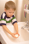 young boy washes hands in bathroom