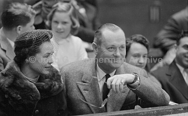 American film and television actor Robert Montgomery (1904-1981) watches tennis match between Pancho Gonzales and Ken Rosewall, Madison Square Garden, 1957.<br />