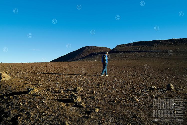 A hiker walks on the barren, moonlike surface inside Haleakala Crater on the island of Maui.