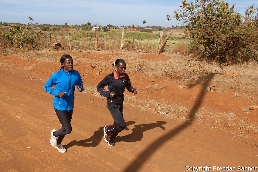 Uganda runner Janet Achola, left, jogging with Kenyan Florence Kiplagat, right,  warming up for a training session outside of Eldoret, Kenya.