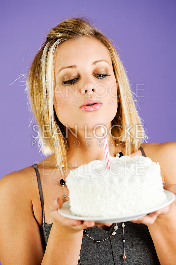 Pretty woman holding birthday cake with candle.