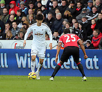 SWANSEA, WALES - FEBRUARY 21: L-R Ki Sung Yueng of Swansea comes up against Antonio Valencia of Manchester United during the Barclays Premier League match between Swansea City and Manchester United at Liberty Stadium on February 21, 2015 in Swansea, Wales.