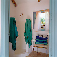 The poolhouse has a simple whitewashed shower room with a tiled floor