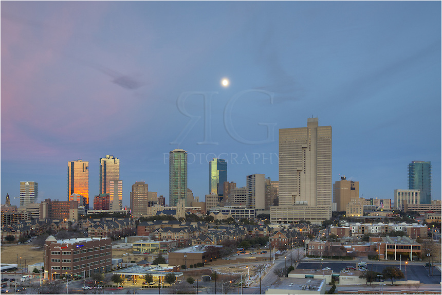 "A view of downtown Fort Worth as the nearly fully moon rises over the city. In the downtown area of ""Cowtown, USA"" you can see architectural structures such as the Tarrant County City Hall, the Wells Fargo Tower, the DR Horton Tower, the Fort Worth Tower, the Carter and Burgess Tower, the Burnett Plaza, the AT&T Building, and the Omni Hotel of Ft Worth."