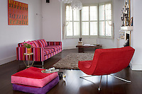 "A contemporary clean and uncluttered living room is furnished with a large pink and purple striped ""Tricia Guild' sofa with a red mid-century modern retro chair  and large matching cushions"