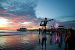 Young people doing gymnastic moves near the Santa Monica Pier at sunset