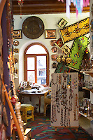 The busy old market bazaar street Kujundziluk with lots of tourist craft and art shops and street merchants. inside of a shop selling jewelleries carpets and various souvenirs. Historic town of Mostar. Federation Bosne i Hercegovine. Bosnia Herzegovina, Europe.