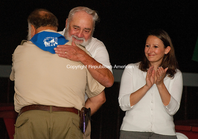OXFORD, CT 11 SEPTEMBER 2013--091113JS0613- Ray Hanley, president of the High Rock Shooting Association, receives a hug from Elio Gugluiotti, Assistant Scout Master for Troop 283 and former Day Camp Director at Camp Mattatuck as Rep. Rosa C. Rebimbas, R-Naugatuck, right, looks on during a picnic for High Rock Shooting Association Wednesday at the Colonial Tavern in Oxford. Hanley was honored with a proclamation from Rebimbas, Rep. David K. Labriola, R-Oxford and Rep. Craig A. Miner, R-Litchfield for his tireless work in promoting gun safety. . Gugliotti thanked him for all the help he gave to Camp Mattatuck. <br /> Jim Shannon Republican American