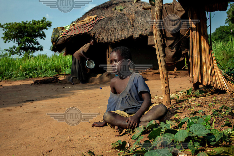 Nine year old Watum Kabila sitting on the ground outside his family's home. Since he was about one year old he has been afflicted by Nodding Syndrome. Little is known about the disease although it is thought that it may be linked to the parasite that causes river blindness. It affects children, usually between 5 and 15 years old, and there is no known cure for the disease. Its cause remains unknown although some people within the communities affected by the illness attribute it to the violence inflicted on the region by Joseph Kony and the Lord's Resistance Army. According to the World Health Organisation 'Nodding Syndrome is characterised by head nodding episodes that are sometimes precipitated by the consumption of food or cold weather. They are often accompanied by convulsions or staring spells. During episodes, a child stops feeding and appears non-responsive, with or without loss of consciousness. There is deterioration of brain function in some victims, and malnutrition with growth retardation in the majority of cases.'.