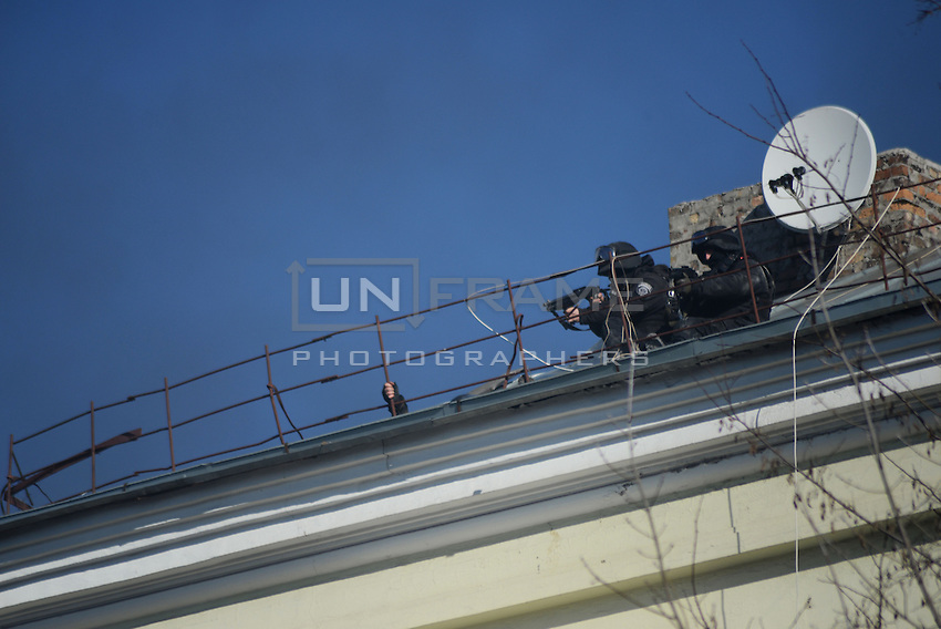 Police forces use machine guns from a rooftop targeting at the protesters in the Maidan square.  Death and injury toll raise every hour on the hour since the violent repression started. Kiev, Ukraine