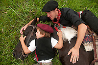 An Argentine horse whisperer teaches his skill to a young boy.