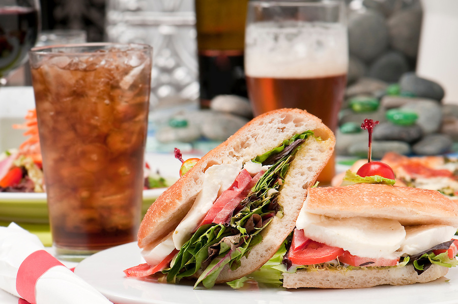 View of mozzarella and tomato sandwich with glass of soda in the background.