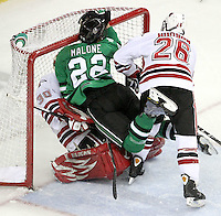 North Dakota's Brad Malone crashes into the net and onto UNO goalie John Faulkner. UNO's Alex Hudson was whistled for interference on the play. No. 8 North Dakota used a three-goal third period to beat No. 4 UNO 6-5 Friday night at Qwest Center Omaha. (Photo by Michelle Bishop)