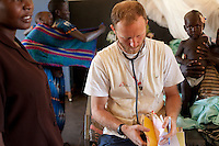 MSF doctor Eamonn Vitt, HIV specialist, treating malria patients on the ward in Madi Opei, Uganda