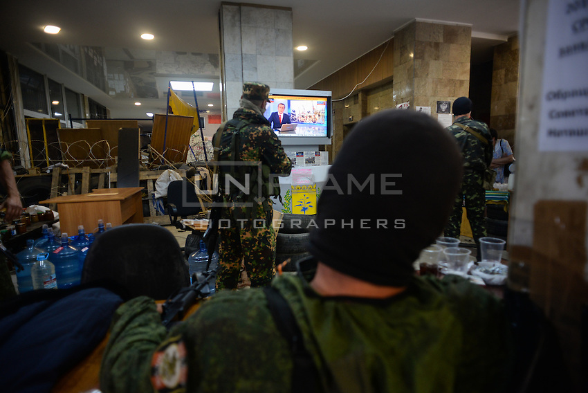 "Member of special pro-Russian battalion ""Vostok"" watching the Russia 24 news channel."