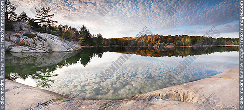 Rocks and autumn trees on a shore of lake George. Beautiful fall nature panoramic scenery. Killarney Provincial Park, Ontario, Canada