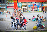 VIETNAM, Ho Chi Minh, Saigon, 3 young people standing next to motorbikes, Motorcycles in the back
