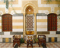 A pair of Moorish chairs and a small table have been placed on a tiled courtyard beside a marble fountain