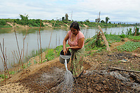 Laos, woman cultivates vegetable field near river, irrigation with river water / Laos, Farmerin baut Gemuese an einem Fluss an, Bewaesserung mit Flusswasser