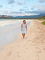 Woman walking Kailua beach with curly hair wearing soft blue dress