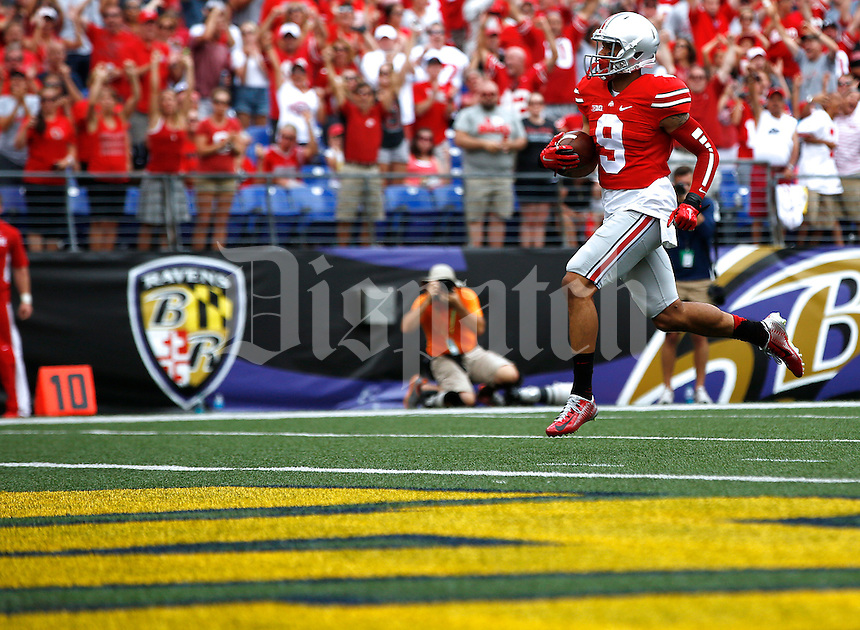 Ohio State Buckeyes wide receiver Devin Smith (9) scores a touchdown after a reception during the third quarter of the college football game between the Ohio State Buckeyes and the Navy Midshipmen at M&T Bank Stadium in Baltimore, Saturday afternoon, August 30, 2014. The Ohio State Buckeyes defeated the Navy Midshipmen 34 - 17. (The Columbus Dispatch / Eamon Queeney)