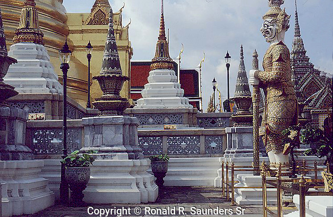"""The Wat Phra Kaew is regarded as the most sacred Buddhist temple in Thailand. It is a """"potent religio-political symbol and the palladium of Thai society"""". It is located in Phra Nakhon District, the historic centre of Bangkok, within the precincts of the Grand Palace."""