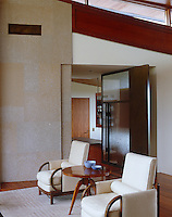 A pair of Rene Gabriel armchairs from the 1940s sit next to a limstone-clad wall in the living room