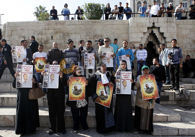 Palestinians hold pictures of prisoner Samer al-Issawi held in Israeli jails during a protest in Jerusalem, in solidarity with hunger-striking detainees held by Israel to demand their release from detention without trial,on Apr. 06, 2013. Photo by Sliman Khader