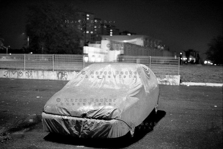 Milano, quartiere Gallaratese, periferia nord-ovest. Una macchina coperta di notte --- Milan, Gallaratese district, north-west periphery. A covered car at night