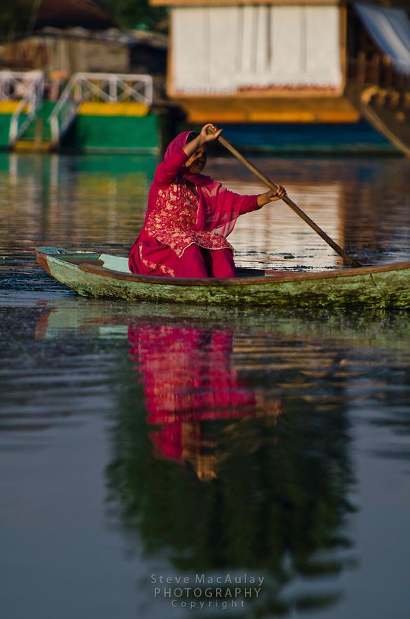 Colorfully dressed Kashmiri woman paddling a traditional shikara on Dal Lake, Srinagar, Kashmir, India.