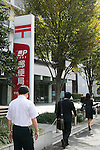 Pedestrians walk past the Japan Post Holdings Co. headquarters on October 29, 2015, Tokyo, Japan. The share price for Japan Post Holdings Co. public offering was set at 1,400 yen (11.58) for its debut on the Tokyo Stock Exchange next November 4. This price was at the high end of expectations and the government hopes that many Japanese citizens will take the opportunity to invest in the company. (Photo by Rodrigo Reyes Marin/AFLO)