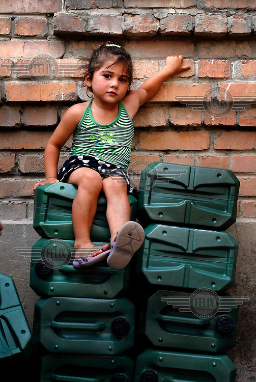 Three year old Salome Beridze, displaced from around the town of Gori, sitting on top of a pile of water containers donated by NGO Save the Children in the Southeast of the country.