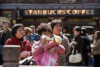Woman feeds baby outside Starbucks in the Yu Garden Bazaar. China has a one child policy to reduce population
