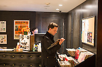 "Doug Robinson looks at the record collection in the lobby of The Verb Hotel in the Fenway neighborhood of Boston, Massachusetts, USA, on Friday, Dec. 4, 2015. The hotel is considered a ""boutique hotel"" and has collections on display throughout the premises of music memorabilia from the Boston area. On the wall of hotel lobby hang pieces of the memorabilia collection of Boston-area rock historian David Bieber."