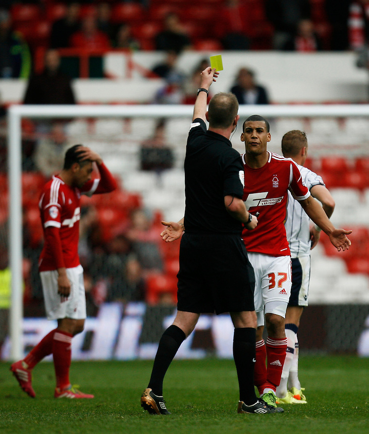 Nottingham Forest's Lee Peltier (R) is shown a yellow card by referee M Brown<br /> <br /> Photo by Jack Phillips/CameraSport<br /> <br /> Football - The Football League Sky Bet Championship - Nottingham Forest v Millwall - Saturday 5th April 2014 - The City Ground - Nottingham<br /> <br /> &copy; CameraSport - 43 Linden Ave. Countesthorpe. Leicester. England. LE8 5PG - Tel: +44 (0) 116 277 4147 - admin@camerasport.com - www.camerasport.com