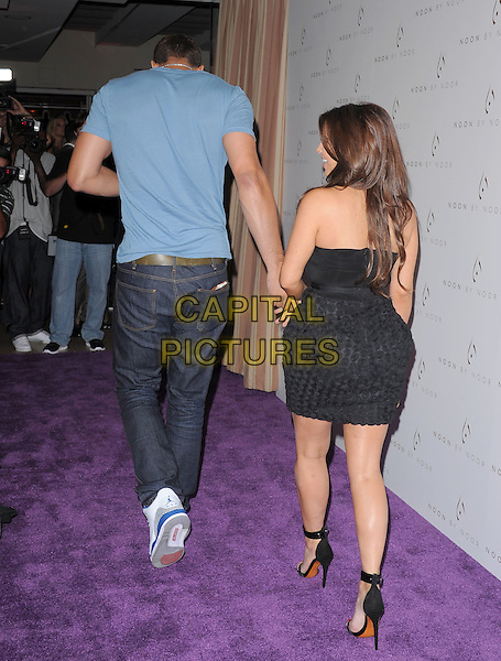 Kris Humphries & Kim Kardashian .The Noon by Noor launch event at At the Sunset Tower in West Hollywood, California, USA..July 20th, 2011         .full length blue t-shirt black strapless dress skirt top circles fiance fiancee engaged couple tall short jeans denim back behind rear.CAP/RKE/DVS.©DVS/RockinExposures/Capital Pictures.
