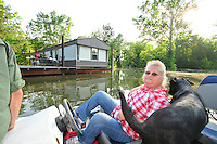"""8/11/11} Vicksburg} -- Vicksburg, MS, U.S.A. -- Mark Bridges,56, thrift store owner, and his dog """"baby girl"""" and his girlfriend of 12 years Patricia Clark, a homeDepot garden employee, cruise down Chicksaw Rd in a bass boat in North Kings Community in Vicksburg Mississippi Wed. May 5th 2011. This is the firs time for Patricia to try and remove things from her trailer, that is built on 9ft stilts  AND THE WATER IS CURRENTLY AT 15 ft. and rising and is less than 12 inches from being flooded. Mark and Patricia have lived their all their lives and will return when the Mississippi River recedes,. ark has been helping his neighbors get their belongings to safety. Vicksburg a riverfront town steeped in war and sacrifice, gets set to battle an age-old companion: the Mississippi River. The city that fell to Ulysses S. Grant and the Union Army after a painful siege in 1863 is marshalling a modern flood-control arsenal to keep the swollen Mississippi from overwhelming its defenses. PHOTO©SUZIALTMAN.COM.Photo by Suzi Altman, Freelance."""