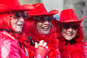 2 March 2014, Duesseldorf, Germany. Pictured: Women with red hats and feather boas. Costumed carnival-goers enjoy the sunshine as they celebrate with a street party in Duesseldorf, North Rhine-Westphalia, Germany.