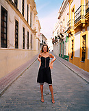 SPAIN, Andalusia, Tarifa, young woman standing on alley amid buildings, portrait