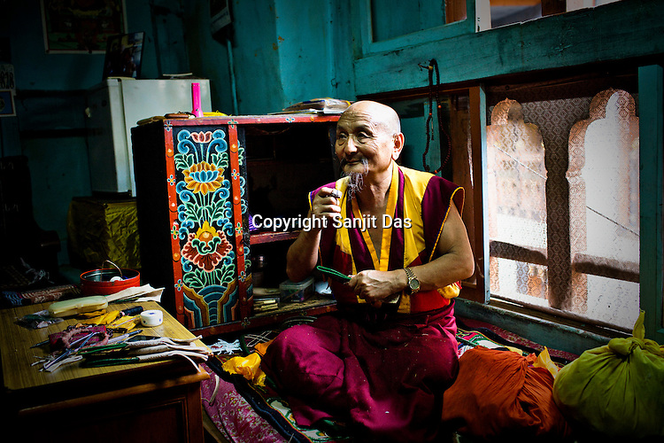A senior Buddhist lama seen sewing in his room at the Punakha Dzong in Punakha, the older capital of Bhutan. Punakha is the administrative centre of Punakha dzongkhag, one of the 20 districts of Bhutan. Photo: Sanjit Das/Panos