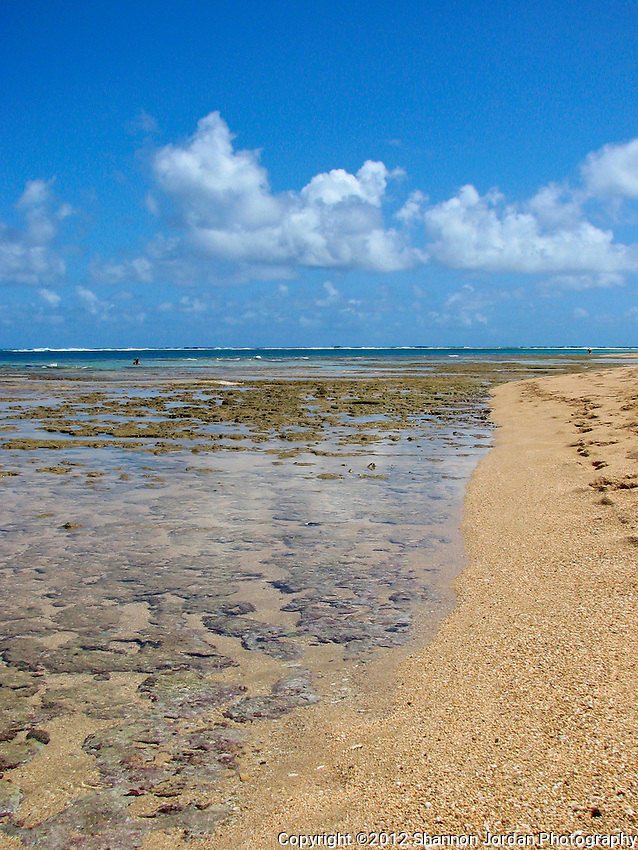 Clouds linger above Tunnels Beach, Kauai. The reef peeks out above the clear, warm water.