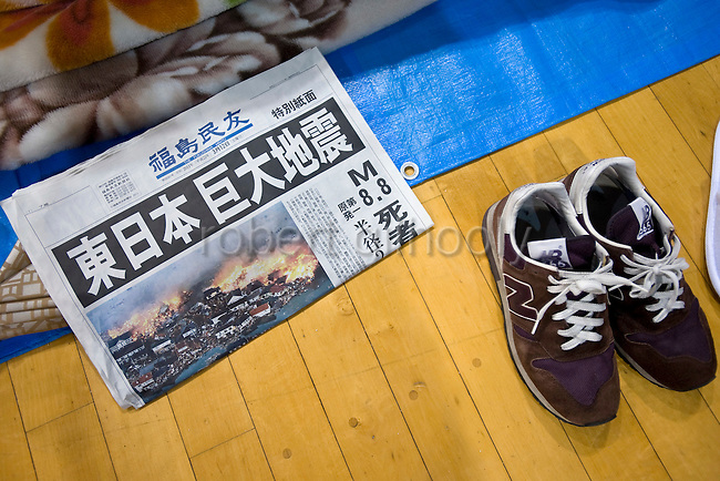 A shoes lies next to a copy of a national newspaper reporting on the magnitude 8.8 earthquake that shook northeastern Japan at a refuge shelter in Iwaki City, northeastern Japan on 12 March, 2011. Around 300 people, many affected by an explosion at a nearby nuclear plant, others by Japan's biggest ever temblor took shelter at the ad hoc shelter set up inside a local gymnasium about 30 km from the nuclear accident.  Photographer: Robert Gilhooly