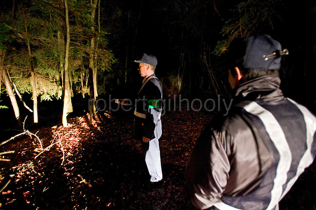 Yasuaki Komaya (L), 56, and Yasunobu Fujie (47) of a Yamanashi Prefectural patrol association check among the trees of Aokigahara Jukai, better known as the Mt. Fuji suicide forest, which is located at the base of Japan's famed mountain west of Tokyo, Japan on 02 Nov. 2009...