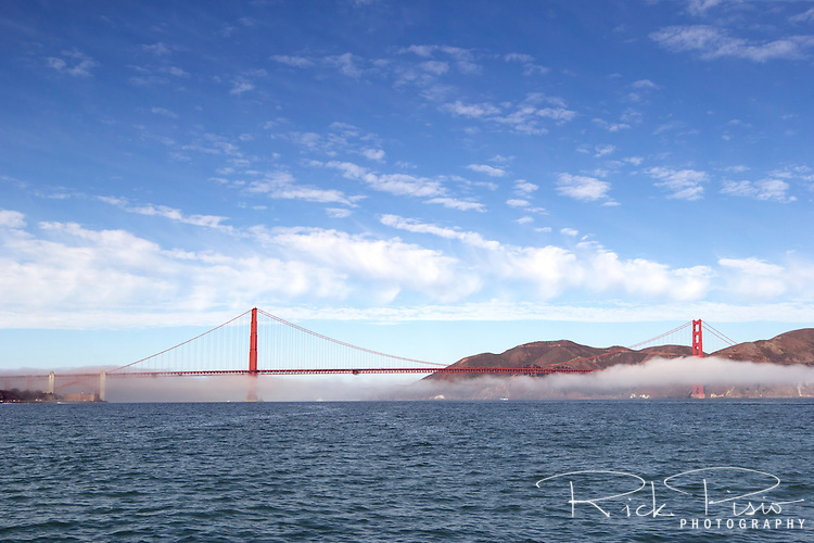 A thin layer of fog hovers just above the waters of San Francisco Bay and below the Golden Gate Bridge.