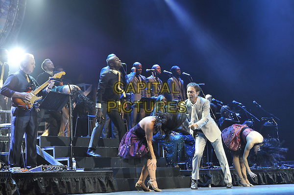 Cliff Richard.Performing live in concert at the O2 Arena, Greenwich, London, England. 25th October 2011.stage gig performance music on full length beige grey gray suit jacket leaning dancing tie bending backup dancers .CAP/MAR.© Martin Harris/Capital Pictures.