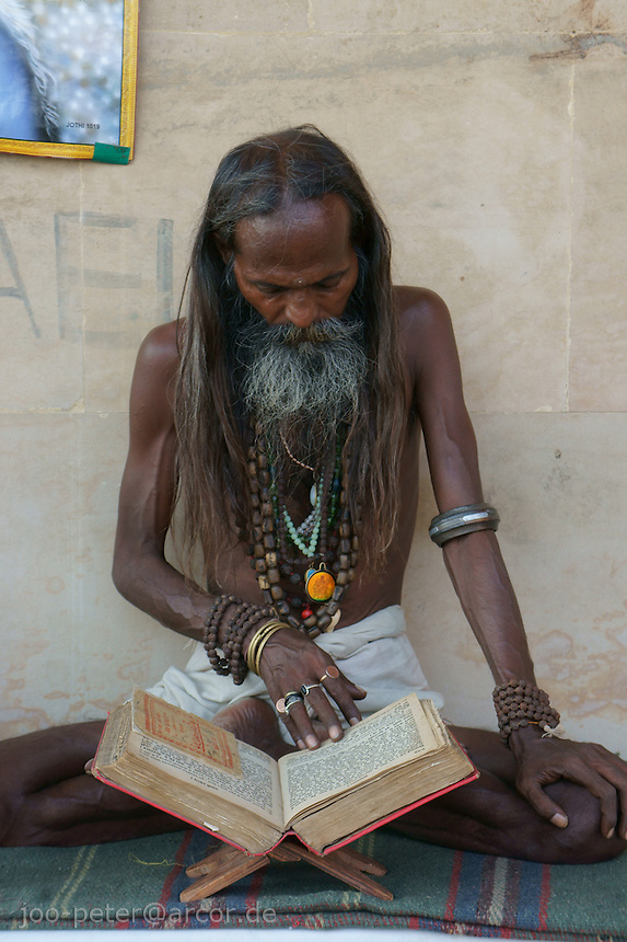 Sadhu reading holy book at River Ganga in Varanasi close to Jalasayi cremation area