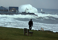 Pictured: A man walks his dog in Porthcawl, south Wales, with huge waves crashing against the lighthouse wall in the distance. Friday 03 January 2014<br /> Re: Flood warnings have been issued  by the Environment Agency due to strong winds and high tides for part of the UK.