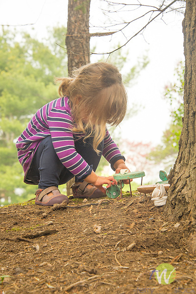 Toddler playing outside with fairy toys.