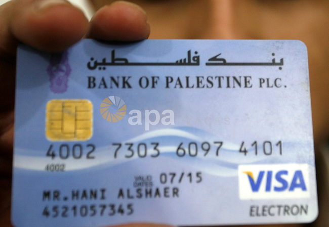 "Palestinian man holds his Visa card in the southern Gaza Strip on January 18, 2012. The attacks were launched against Israeli sites at the beginning of this month when a Saudi internet expert called (0xomar) published details of thousands of Israeli credit cards and personal details of their holders. According to Israeli reports the pirates of the Internet who support the Palestinians were able to penetrate sites belonging to the Israeli banks. An Israeli expert in electronic security systems said that the pirate attacks suffered by the Israeli Web sites were smart, and half of the computers that were used were from within ""Israel"", while experts said the site had been attacking Israeliاpolice website. Photo by Abed Rahim Khatib"