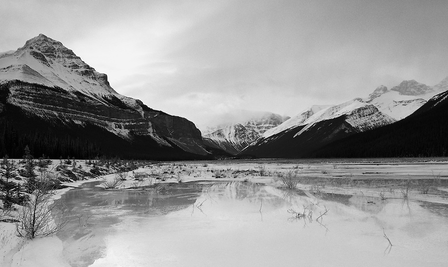 Ice reflects the nearby mountains in a pond near the Icefields Parkway in Alberta Canada.